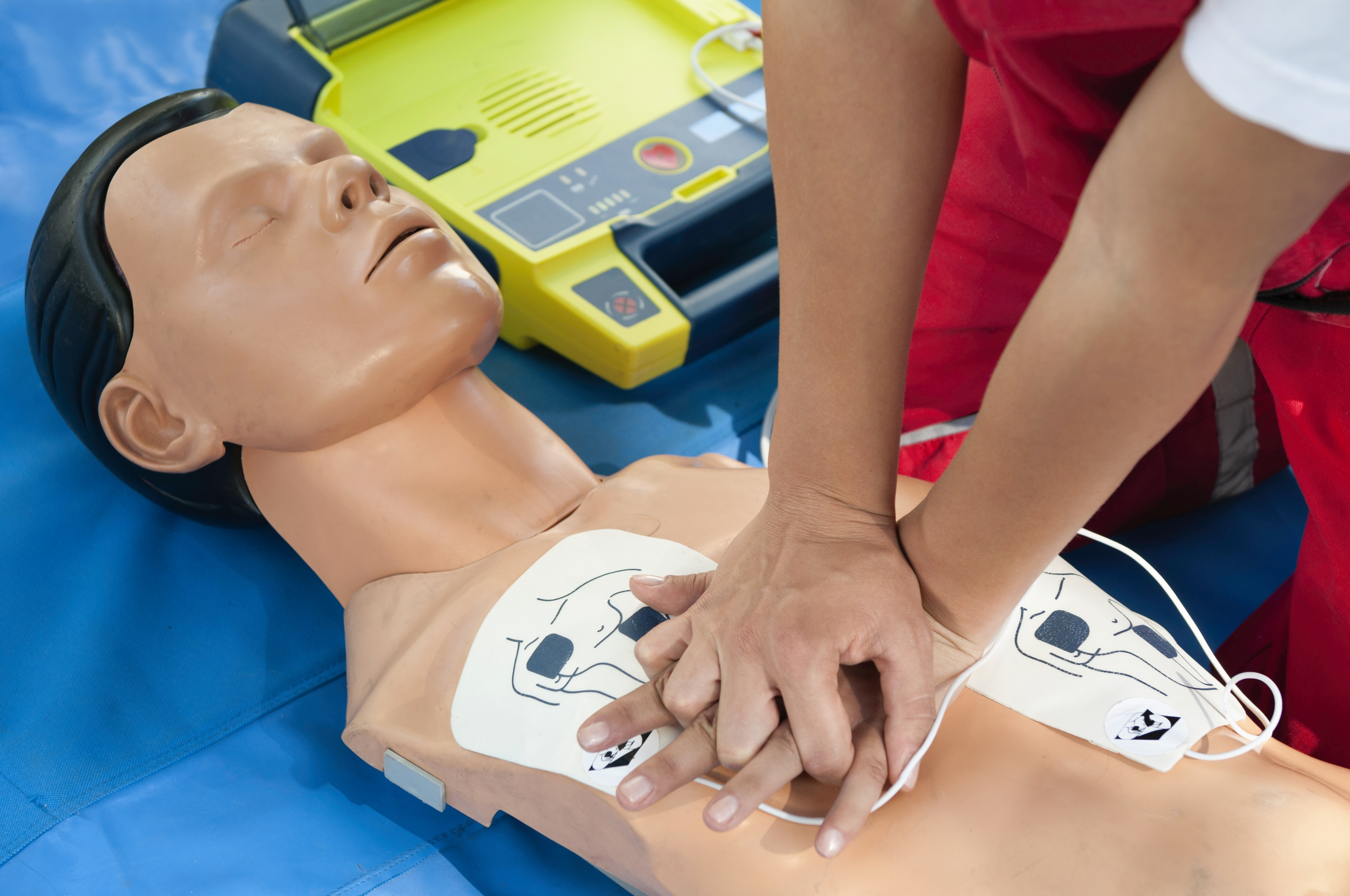 CPR training - Chest compressions combined with AED defibrillator operation performed on a CPR dummy. Focus on hands
