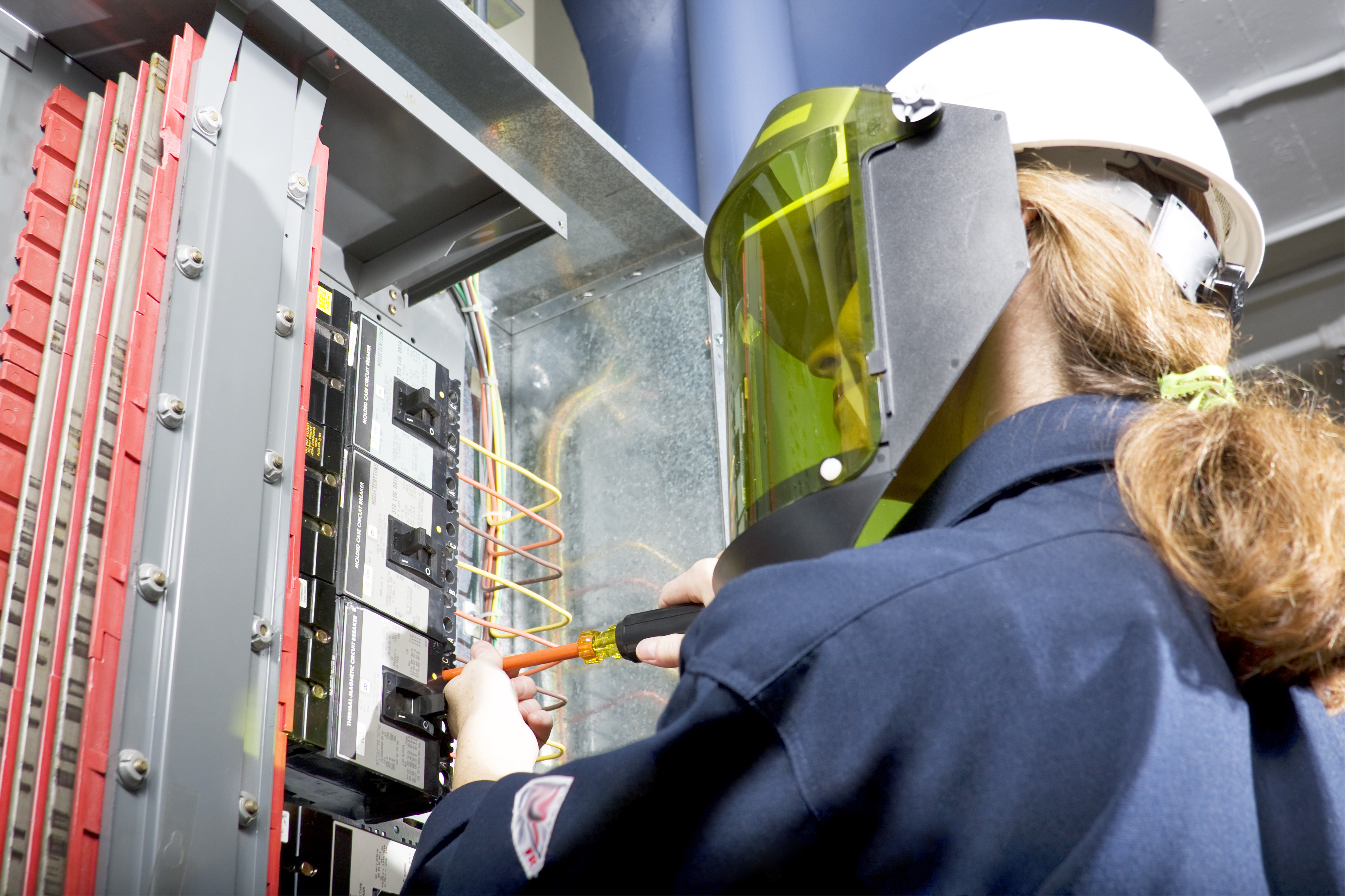 woman wearing a face mask to protect herself from electrical shocks while inspecting a electrical panel.