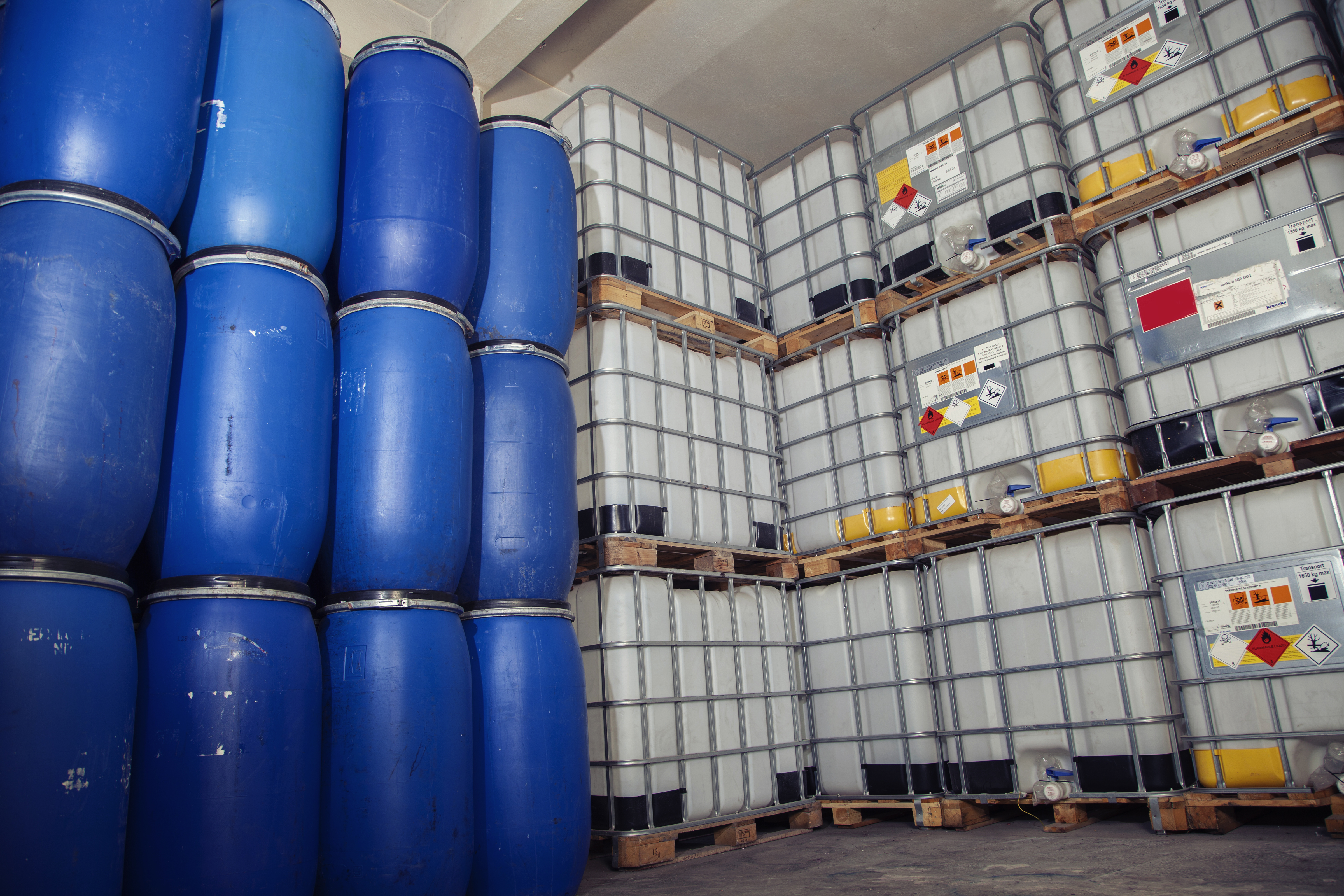 containers and tubs holding dangerous goods and chemicals with WHMIS symbols on stickers.