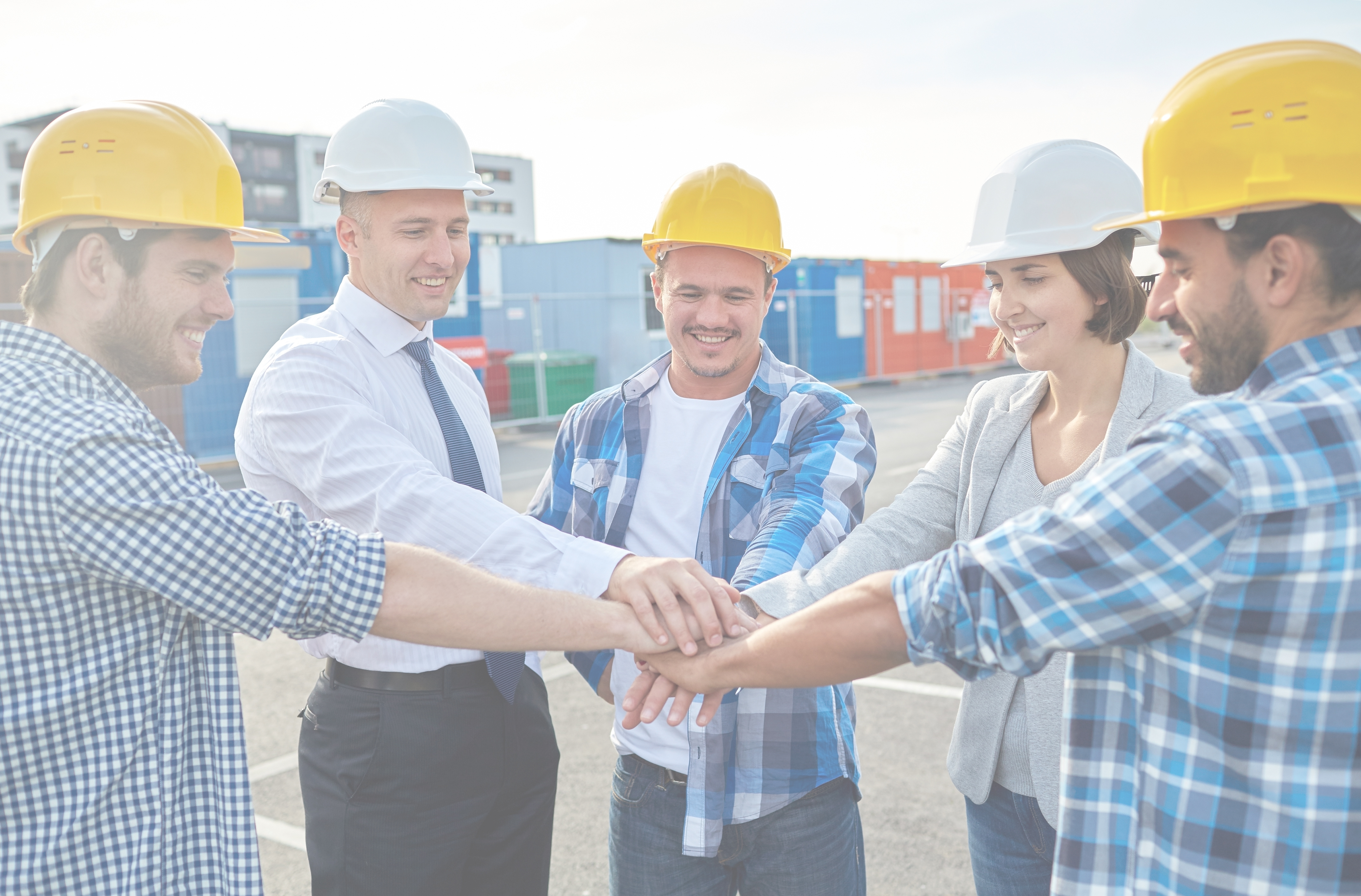 positive safety culture business, building, partnership, gesture and people concept - smiling builders and architects in hardhats with hands on top outdoors