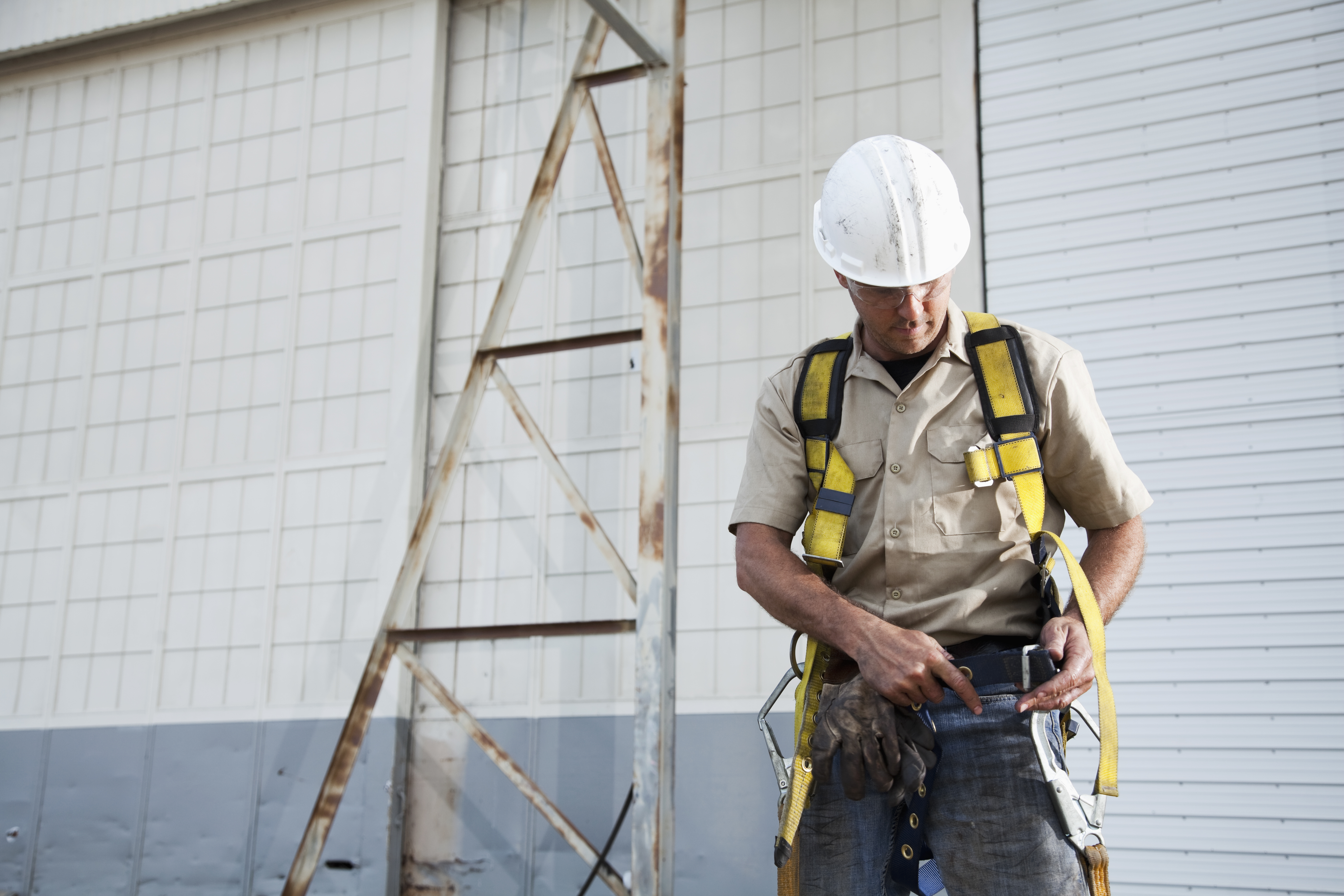 """Worker (30s) with work gloves, hard hat, safety glasses, putting on harness."" working at heights training. fall protection equipment"