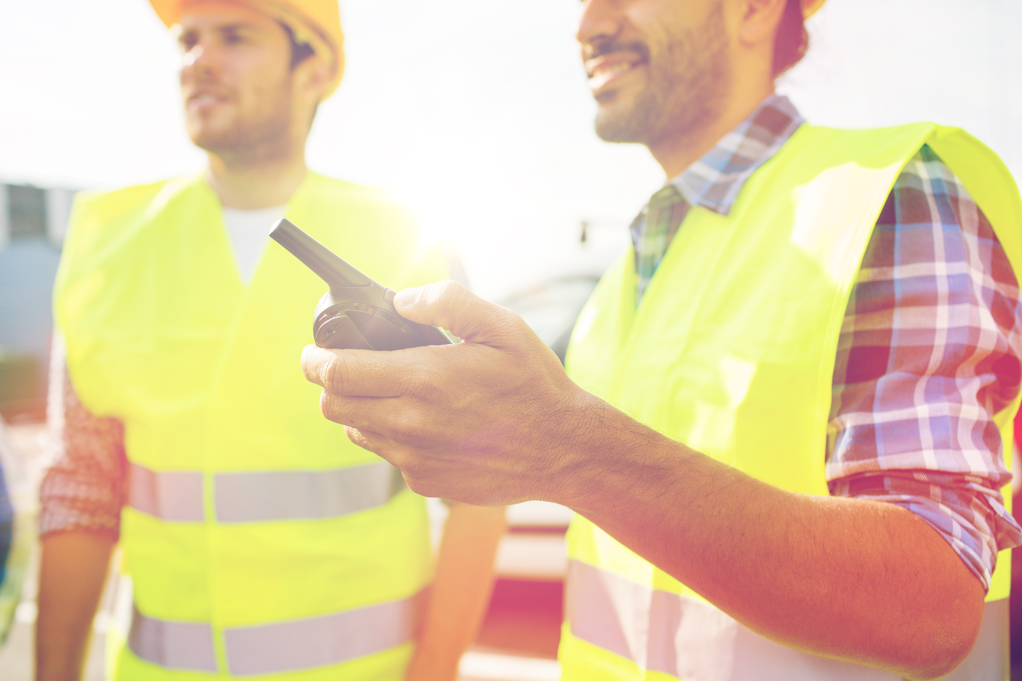 industry, building, technology and people concept - close up of male builders in high visible vests with walkie talkie or radio outdoors