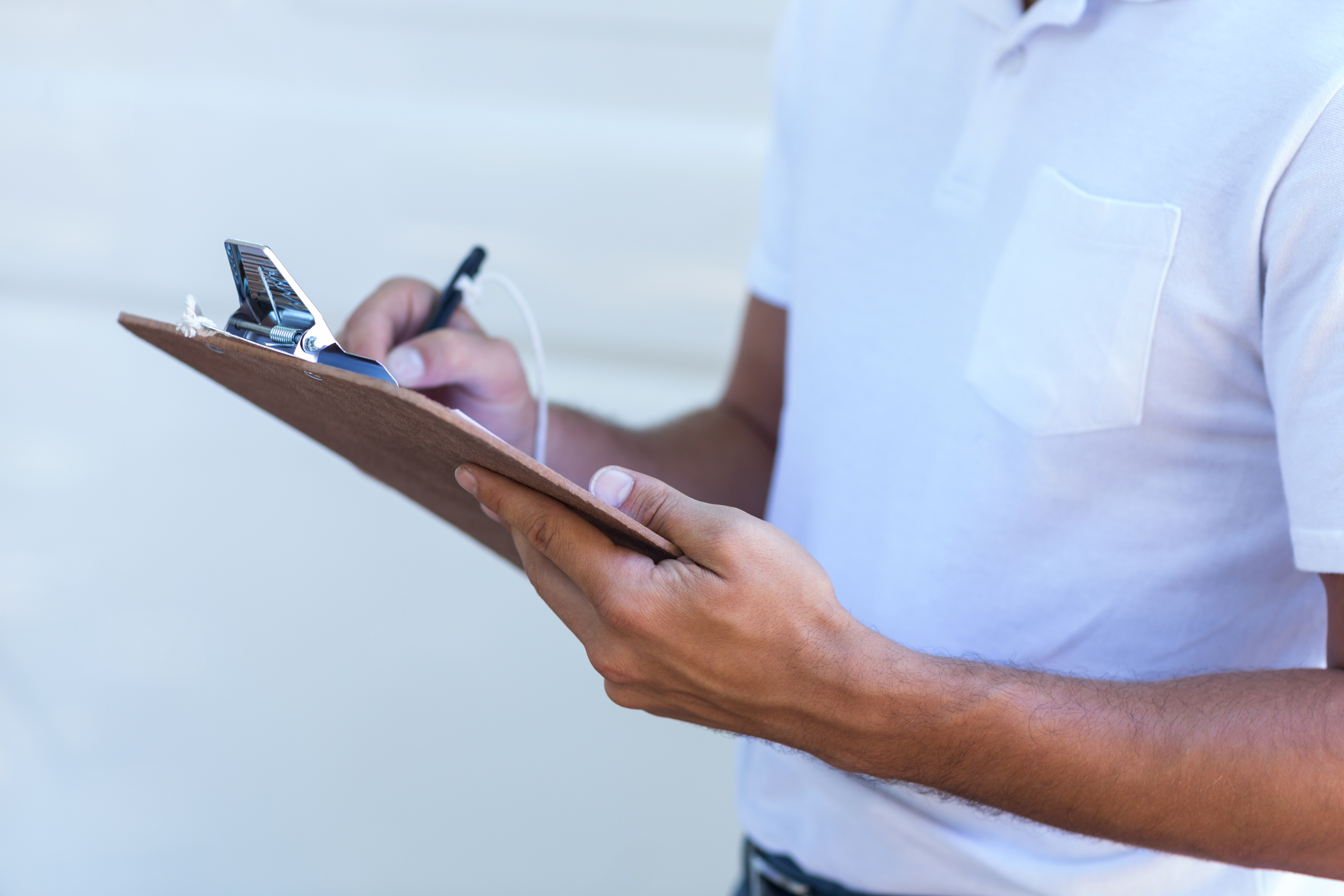 Midsection of delivery man writing in clipboard