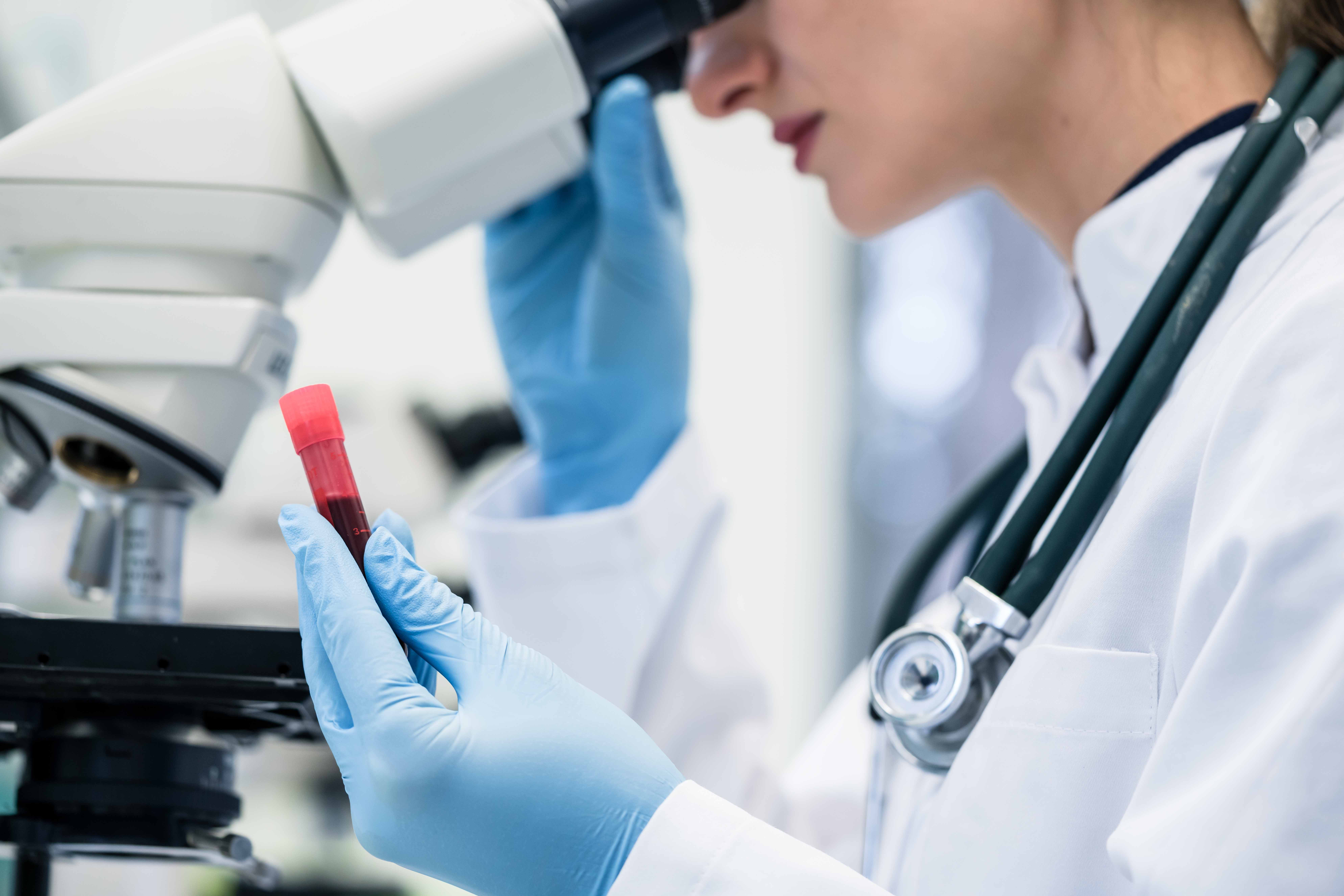 Woman examining blood sample under microscope in medical or scientific laboratory