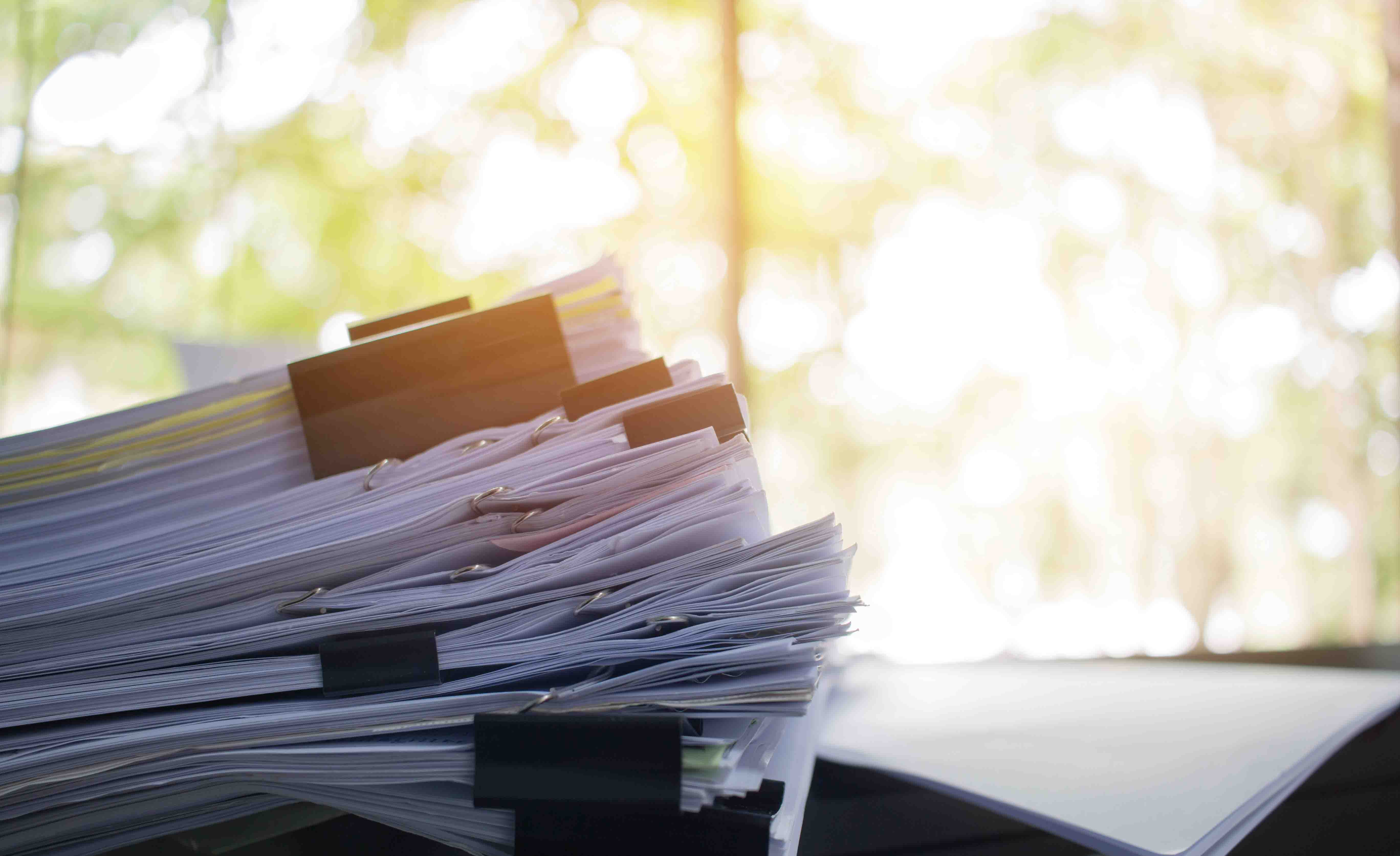 Stack of paper files on work desk in office