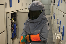 A welder putting on personal protective equipment