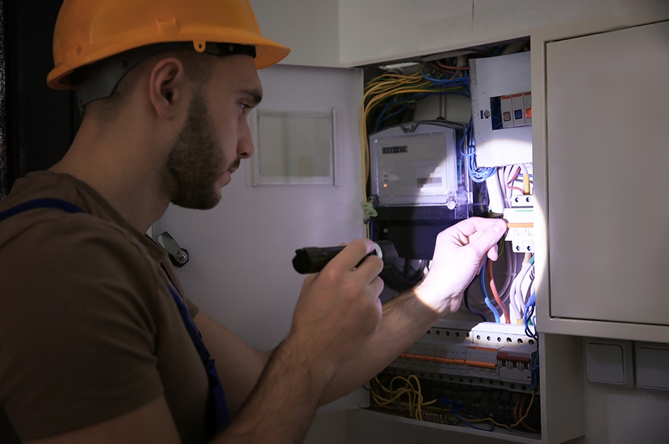 Worker examining an electrical panel
