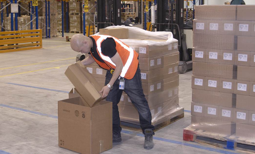 Worker lifting boxes in warehouse