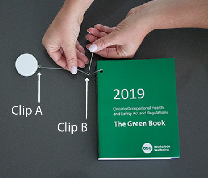Green Book with Retractable Cord Attached and Clips on Cord - upper clip labelled A, lower clip labelled B