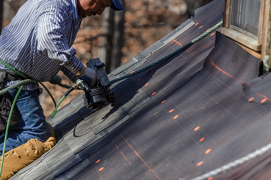 Roofer placing shingles