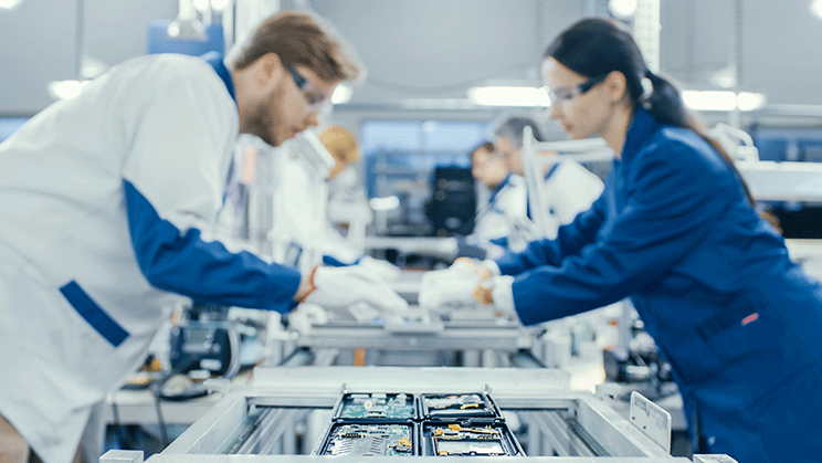 Man and woman leaning over assembly line working