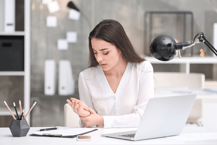 Woman at desk holding painful wrist