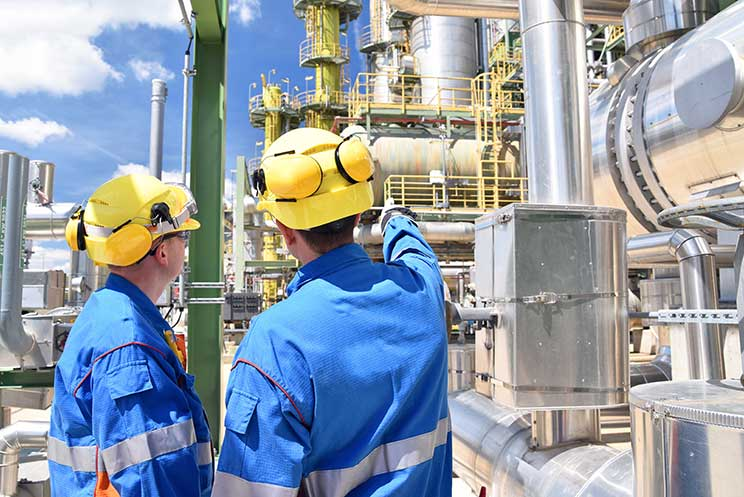 Two people wearing hard hats doing inspection of chemical plant
