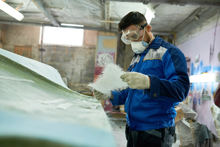 mature man wearing protective mask repairing boat while working in yacht workshop