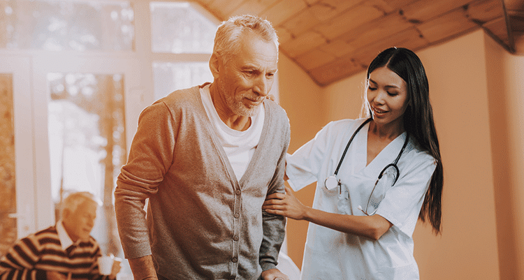 Nurse helping senior man walk