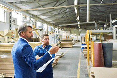 Man wearing suit with clipboard inspecting warehouse with worker