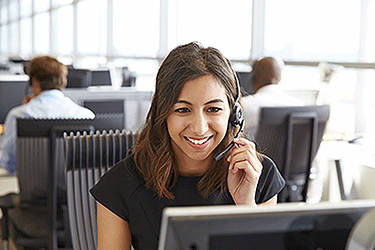 woman sitting at a desk wearing hands free headset while talking to a customer