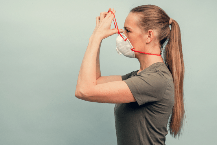 A woman is putting on a protective mask