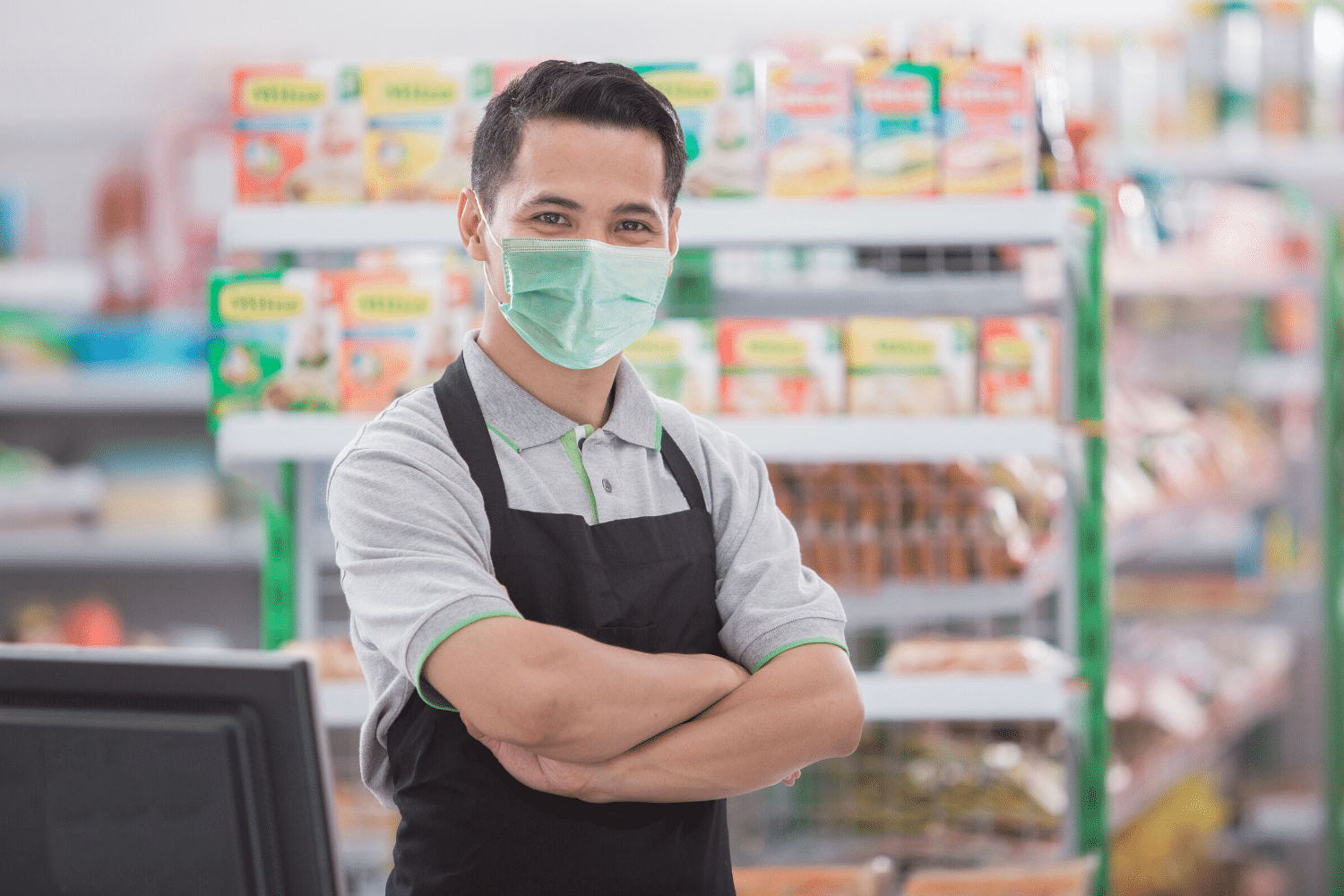 Happy grocery store clerk wearing a face mask
