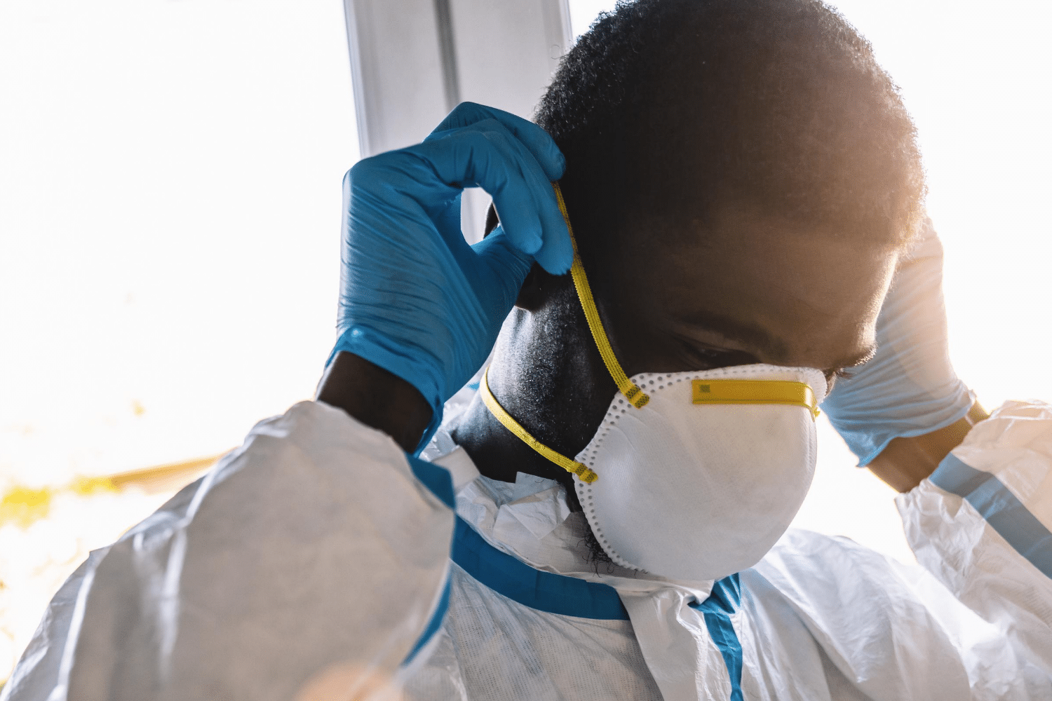 Man wearing disposable gloves donning a respirator